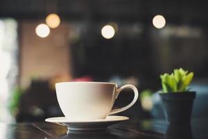 xícara de café com cacto na mesa de madeira foto