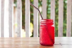 bebida gelada em copo vermelho em uma mesa de madeira do lado de fora foto