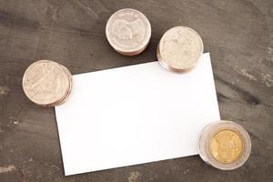 cartão de nome em branco com moedas em uma mesa
