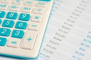 close-up de uma calculadora azul e finanças