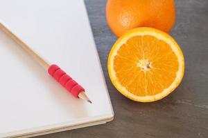 lápis em um caderno ao lado de laranjas
