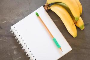 caderno com um lápis verde e bananas