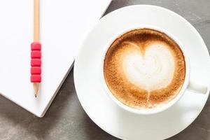 xícara de café com bloco de notas e lápis em uma superfície cinza