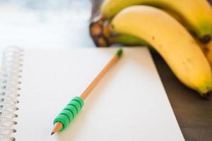 lápis verde em um caderno com frutas