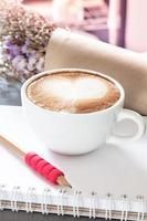 café com leite e lápis em um caderno com flores