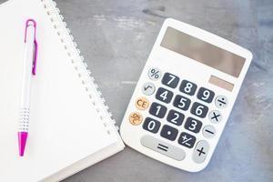 calculadora e bloco de notas em um fundo cinza