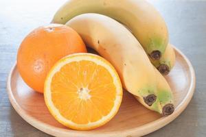close-up de uma tigela de frutas com laranjas e bananas