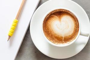xícara de café com um bloco de notas em um fundo cinza