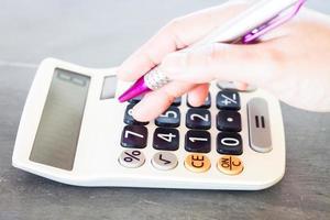 a mão de uma mulher com uma calculadora e uma caneta