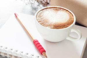 café com leite e lápis em um caderno
