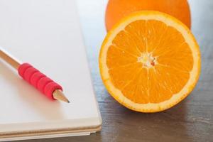 laranjas ao lado de um caderno