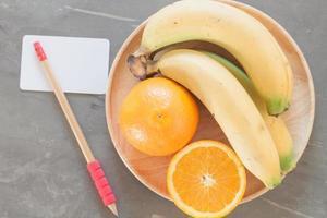 tigela de frutas com um lápis e um cartão de visita
