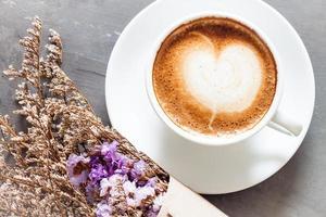 café com leite e flores em uma mesa cinza