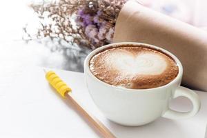 xícara de café com bloco de notas e lápis em um fundo cinza