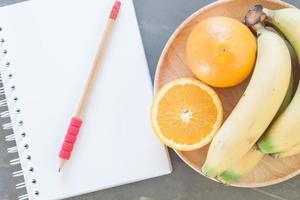 caderno e lápis ao lado de uma tigela de frutas