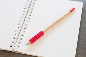 caderno com um lápis vermelho