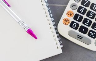 close-up de uma caneta, caderno e uma calculadora