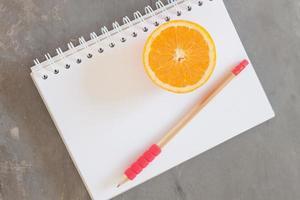 lápis e laranja em um caderno
