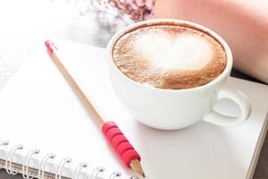 café com leite com um lápis em um caderno