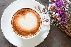 café com leite e flores em um fundo cinza