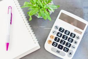 caderno com uma caneta, calculadora e uma planta