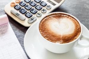 xícara de café e calculadora