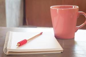 xícara de café rosa com um lápis e um caderno
