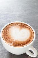 close-up de um café com leite em um fundo cinza