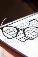 óculos em um laptop foto
