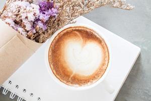 vista superior de um café com leite em um caderno com flores