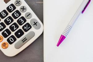 close-up de uma caneta e uma calculadora