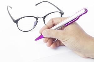 mão escrevendo com óculos foto