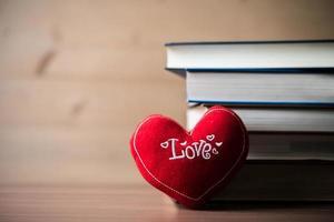 coração vermelho e livro na mesa de madeira foto