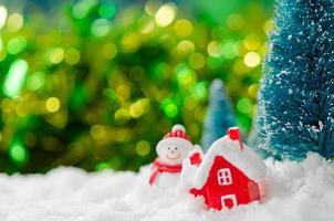boneco de neve em miniatura e casa na neve foto