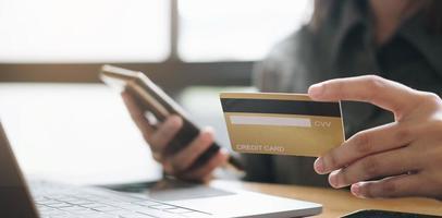 mãos segurando um cartão de crédito e usando laptop