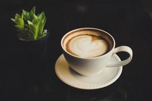 Café com leite em forma de coração com cacto na mesa