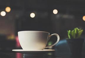 xícara de café com cacto na mesa de madeira