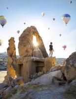 homem parado em uma colina rochosa, balões de ar ao redor