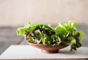 salada de alface verde fresca em prato de madeira. foto