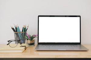 tela do laptop em branco na mesa com suprimentos para o espaço de trabalho