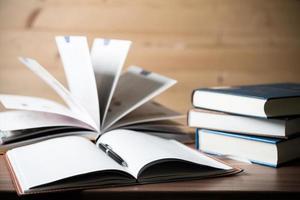 close-up de livros abertos na mesa de madeira foto