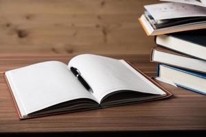 pilha de livros abertos em uma mesa de madeira