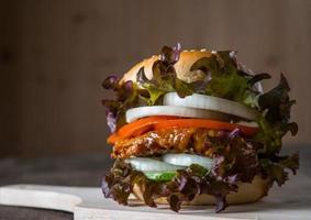hambúrguer caseiro de frango com alface, tomate e cebola