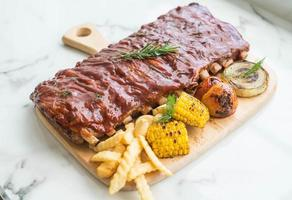 Costelas grelhadas para churrasco com legumes e batatas fritas na tábua de madeira