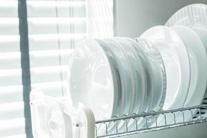 pratos limpos e brancos em um suporte para pratos