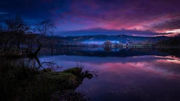pôr do sol roxo com reflexo do lago