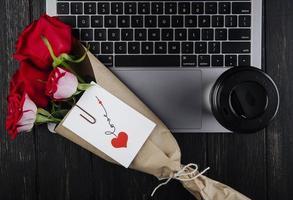 vista de cima um buquê de rosas e uma xícara de café em um laptop