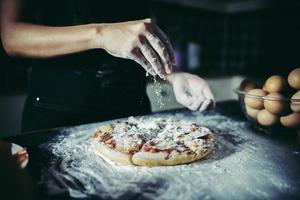 mãos do chef derramando farinha na massa crua