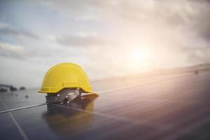 capacete de segurança amarelo no painel solar foto