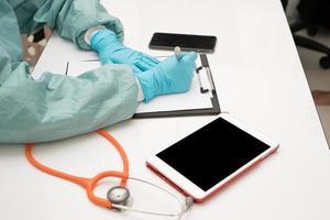 médica escrevendo em seu escritório foto